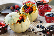French melons filled with berries: blueberries, strawberries, blackberries and redcurrants.
