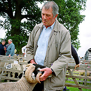 Hill farmer, Derek Dowkes shows a Swaledale tup (ram) at Farndale Show, North York Moors, North Yorkshire, UK