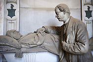 Pictures of a son and his dying father, In memory of a Portuguese patrician Battista Noli Da Costa. Sculpted in a realistic style by Risorgimento sculptor S Saccomanno in 1887, Section A, no 3, Staglieno Monumental Cemetery, Genoa, Italy .<br /> <br /> Visit our ITALY PHOTO COLLECTION for more   photos of Italy to download or buy as prints https://funkystock.photoshelter.com/gallery-collection/2b-Pictures-Images-of-Italy-Photos-of-Italian-Historic-Landmark-Sites/C0000qxA2zGFjd_k<br /> If you prefer to buy from our ALAMY PHOTO LIBRARY  Collection visit : https://www.alamy.com/portfolio/paul-williams-funkystock/camposanto-di-staglieno-cemetery-genoa.html