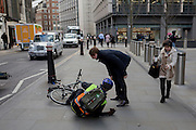 A cyclist lies shocked on the pavement, after being blown over as Storm Doris blows across the UK and pedestrians on Fenchurch Street, brave the high winds funneled through the narrow streets, squeezed between the tall buildings of financial and insurance institutions in the City of London, on 23rd February 2017. Strong winds have led to flight cancellations and road and rail disruption across much of Britain. Thousands of homes have been left without power in Northern Ireland, Wales, Scotland and northern England.