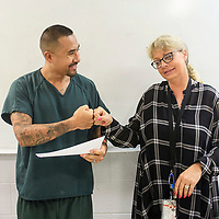 Erika Hayes gives Daren Simeona a fist bump as she congratulates him on completing a 28 day substance abuse treatment program. Hayes is the treatment program manager and held a luncheon for the four graduates of the program, Wednesday, July 18 at the McKinley Adult Detention Center.