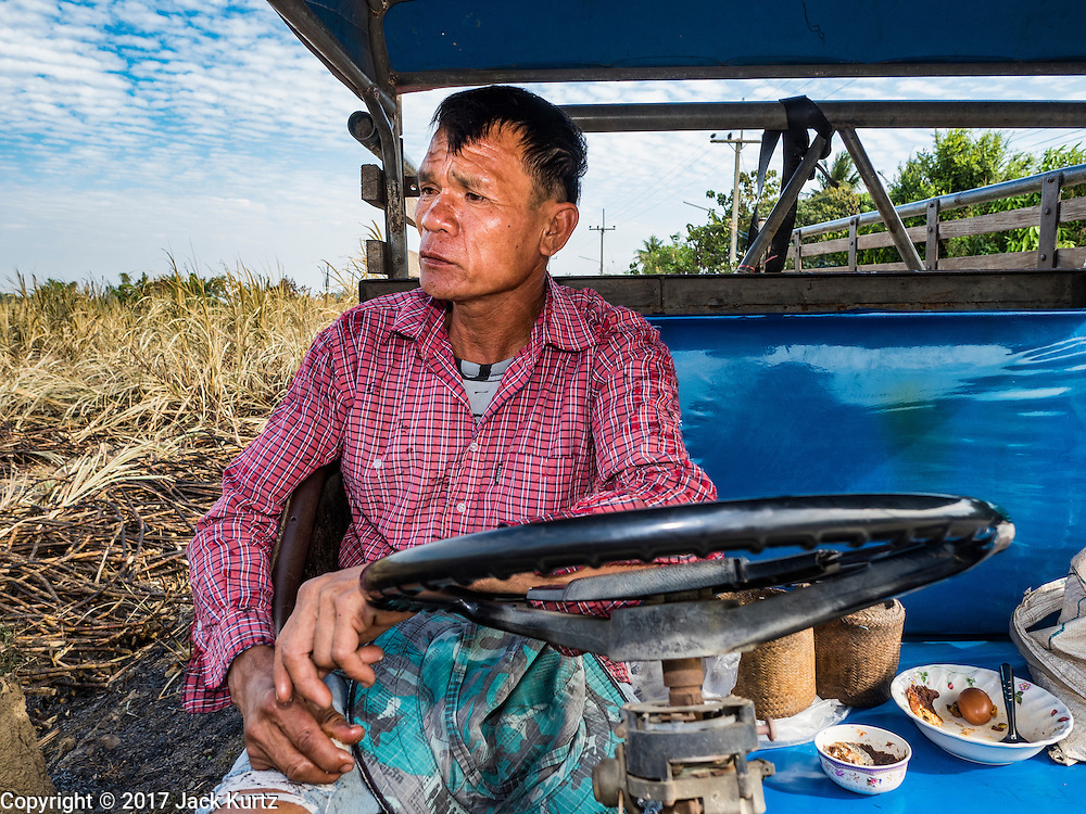 24 JANUARY 2017 - PHRA THAEN, KANCHANABURI, THAILAND: The crew chief on a sugarcane cutting crew waits for his workers to clear a field on a sugarcane plantation in Phra Thaen. Thai government  officials recently announced that they plan to float sugar prices later this year or early in 2018. Wholesale prices are currently set by the Cane and Sugar Board, a part of the Industry Ministry, while the Commerce Ministry sets the retail price. Thailand has fixed retail prices of sugar to guarantee a profit for farmers. Thailand is the world's leading exporter of sugar, after Brazil. Thai sugar production is expected to drop by more than three percent because of the lingering drought that crippled agriculture through 2015 and 2016.    PHOTO BY JACK KURTZ
