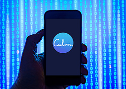 Person holding smart phone with Calm company logo displayed on the screen. EDITORIAL USE ONLY