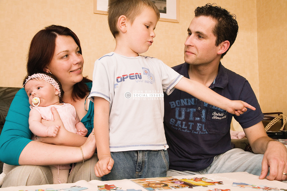 Polish mother and baby daughter look on as father and son play with jigsaw together,