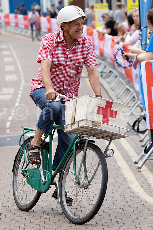 A male cyclist riding a vintage bicycle with old fashion Red Cross basket cycles during the 7th Prudential RideLondon Surrey Classic on the 4th August 2019 in Kingston upon Thames in the United Kingdom.