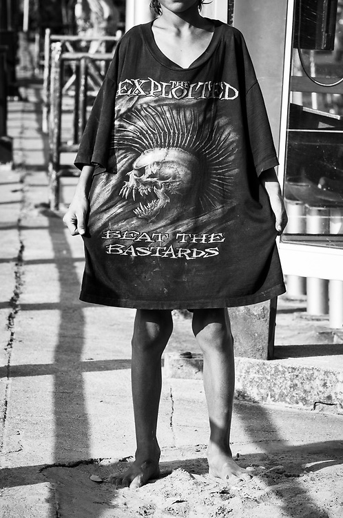 A boy on a street in Chiang Mai wears a shirt depicting the cover art of Beat the Bastards, an album released in 1996 by the Scottish punk group The Exploited. (November 26, 2011)