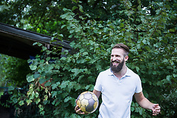 Happy young man playing football in garden, Bavaria, Germany