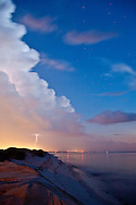 There is an amazing assortment of light in this image- ground glow from a nearby city, twilight, lightning glow within the cloud and from the bolt, light from a full moon, and a streetlight behind the camera.