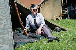 A female re-enactor portrays a Wehrmacht Heferin with the German Army in work uniform blouse shelters from the sun in the shade of a Zeltbahn. Wehrmacht Heferinnen were he German Armed Forces female Auxiliaries. At various periods of time during world war two they were sometimes classified as military personnel other times as uniformed civilians employed by the German Armed Forces (Wehrmacht)<br />  <br /> 04 July 2015<br />  Image © Paul David Drabble <br />  www.pauldaviddrabble.co.uk