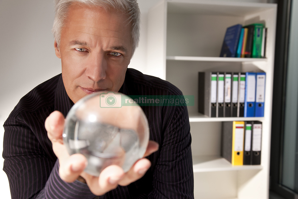 Mar. 19, 2010 - Businessman holding a crystal ball. Model and Property Released (MR&PR) (Credit Image: © Cultura/ZUMAPRESS.com)