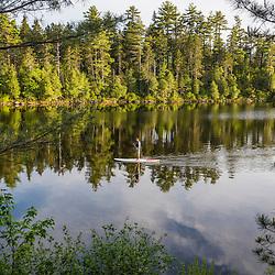 A man paddleboarding on Long Pond near the Appalachian Mountain Club's Gorman Chairback Lodge. Near Greenville, Maine.