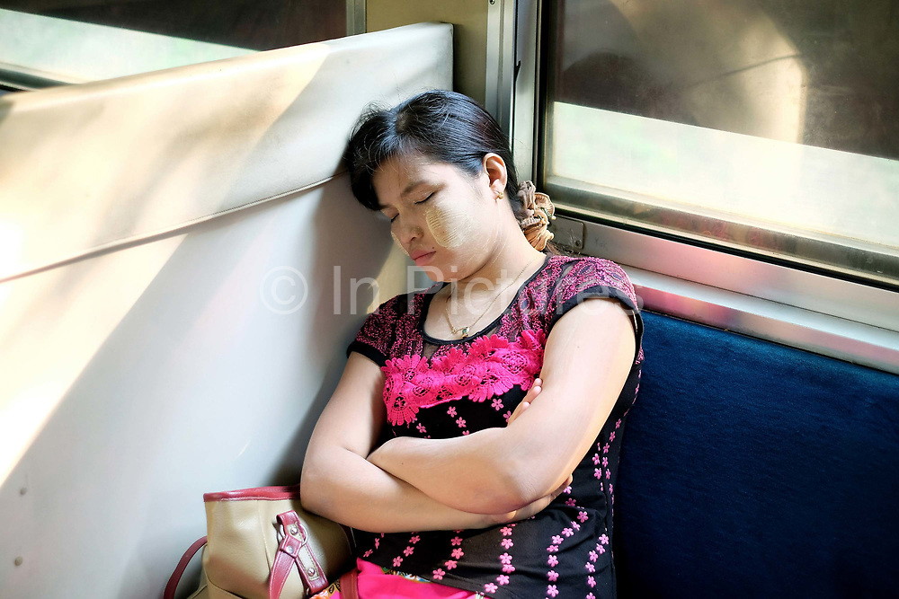 A sleeping passenger on the Yangon Circular Railway on 16th May 2016 in Myanmar. The railway, a narrow gauge local commuter trail network serving Yangon metropolitan area is a 28.5 mile 45.9 km 39 station loop system. This British built rail-loop connects Yangon to its satellite towns and villages