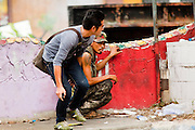 18 MAY 2010 - BANGKOK, THAILAND: Men take cover from suspected snipers at Din Daeng Intersection in Bangkok Tuesday. The intersection has been under periodic sniper fire from unidentified snipers near Thai military lines. Violent unrest continued in Bangkok again Tuesday nearly a week after Thai troops started firing on protesters and Bangkok residents took to the streets in violent protest against the government. Tuesday was not as violent as previous days however. Although protesters continued to set up roadblocks and flaming tire barricades across parts of the city, there was not as much gunfire from the government lines. The most active protesters were at the Din Daeng Intersection about a mile from the Red Shirts' Ratchaprasong camp.  PHOTO BY JACK KURTZ