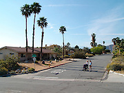Two teenagers with baby cart in a desolate neighborhood in Palm springs USA.