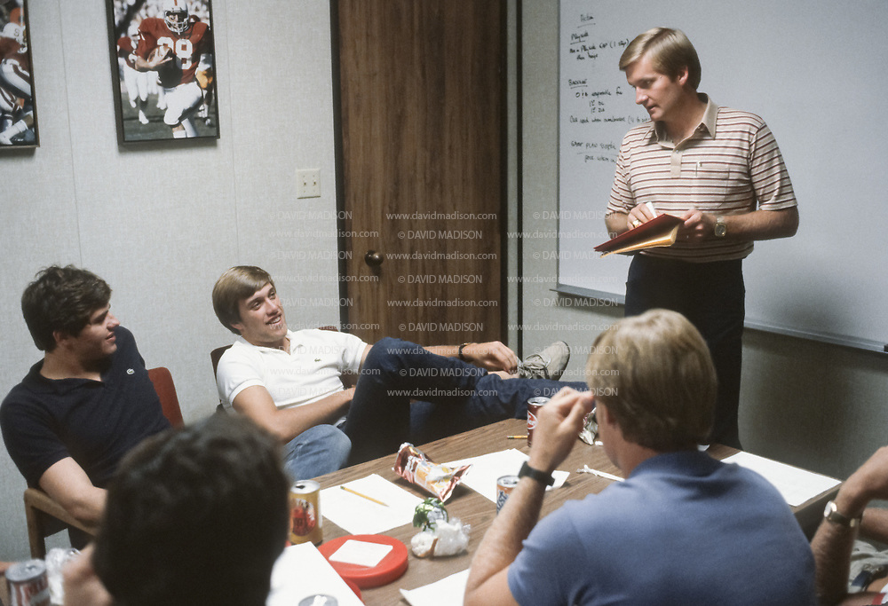 PALO ALTO, CA - OCTOBER 1982:  Stanford Cardinal Offensive Coordinator Jim Fassel (standing, at right) works with Stanford quarterbacks including John Elway (white shirt) during a meeting in October 1982 at Stanford University in Palo Alto, California.  (Photo by David Madison/Getty Images)