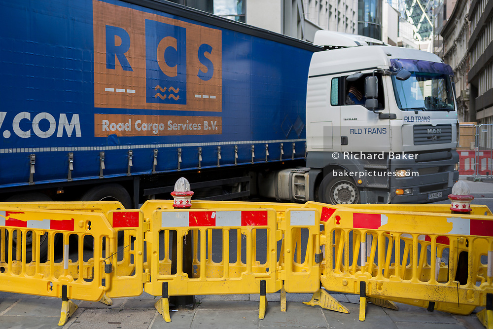 After taking a wrong turn after a road closure, a Dutch HGV lorry reverses at its maximum angle in Fenchurch Street, a narrow highway in the City of London, the capital's financial heart, on 25th September 2018, in London, England.