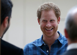 Prince Harry talks to staff before watching a rehearsal of the Joyful Noise choir, a group from NAZ, a sexual health charity for minority communities, at The Hurlingham club in London.