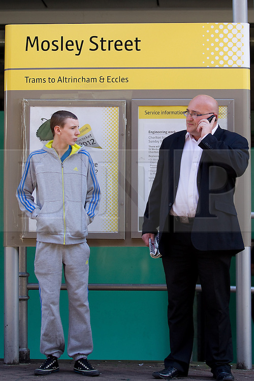 © Licensed to London News Pictures .  08/09/2012 . Manchester, UK . Domenyk Noonan (right) , recently released from prison , at Mosley Street tram stop , Manchester , accompanied by his Nephew , Kieran Noonan (left) . The area was the scene of looting and rioting on 9th August 2011 , during which Noonan was arrested . Noonan has announced he plans to sue the police over the  arrest . Under the terms of a previous early release , the arrest lead to him being recalled to prison . Photo credit : Joel Goodman/LNP