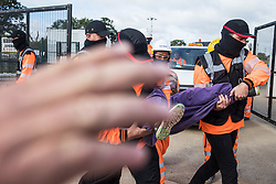 A security guard working on behalf of HS2 obstructs the photographer's camera as his colleagues forcibly remove environmental activists from HS2 Rebellion from the road in front of a gate providing access to a site for the HS2 high-speed rail link on 12 September 2020 in Harefield, United Kingdom. Anti-HS2 activists continue to try to prevent or delay works on the controversial £106bn HS2 high-speed rail link in the Colne Valley where thousands of trees have already been felled.