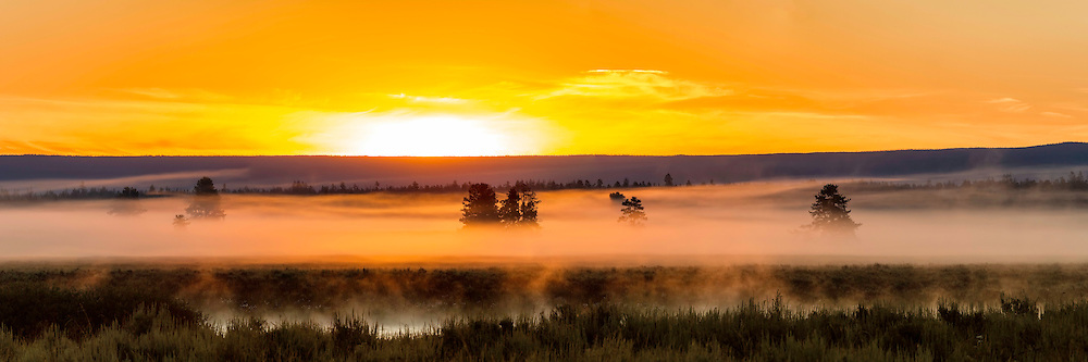 Fog lifts off of the Henry's Fork River on a cool Summer monring and the sun begins to glow on the horizon.