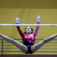 Nadine Joy Nathan of Raffles Girls' School executes her uneven bar routine during the 6th Singapore Gymnastics National Championships at Bishan Sports Hall on February 22, 2014, in Singapore.