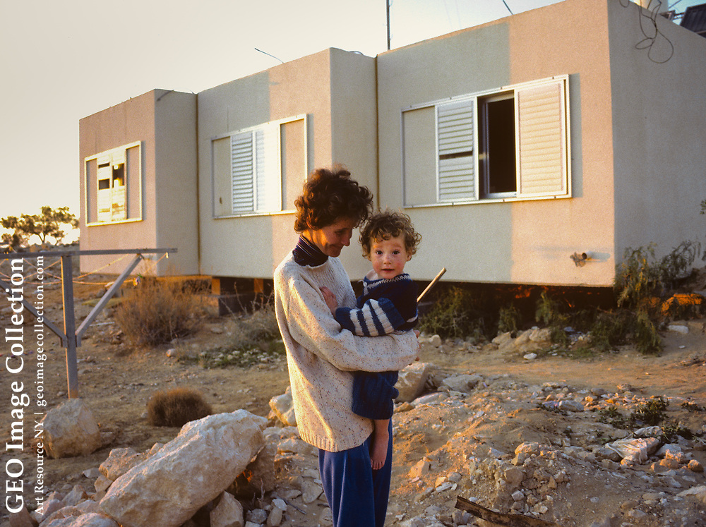 Young Israeli mother holds up her toddler at  a startup settlement in the Negev Desert, Israel near Nizzana. The Jewish three families here make a living by raising goats or doing other jobs for wages.  Leah Desau is the mother with son young Barach. The Jewish Agency plans the housing and development at new settlements consistent with Zionist ideals.