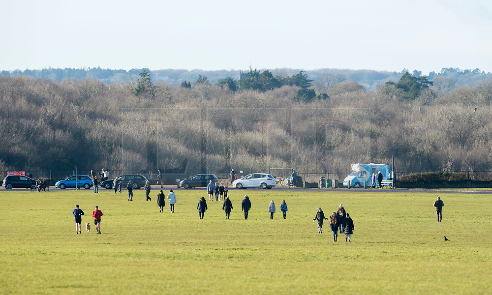 © Licensed to London News Pictures; 23/01/2021; Bristol, UK. People take exercise including with dogs, walking on Bristol Downs in the west of the city as England is under a third national lockdown since the start of the Covid-19 coronavirus pandemic after a new strain of a more infectious Covid virus has spread through the country. Ahead of this weekend Bristol City Council had asked residents to only use their nearest park, saying that major parks across the city such as The Downs, Ashton Court Estate, Blaise Castle Estate and Oldbury Court Estate were becoming very busy at the weekends. People are asked to try to use the nearest park or green space to their home for exercise. Government guidance says that exercising locally is a reasonable excuse to leave home, but what local means exactly has not been defined. Photo credit: Simon Chapman/LNP.