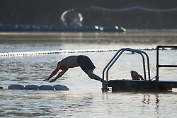 © Licensed to London News Pictures. 24/09/2018. London, UK. Swimmer at sunrise in the Serpentine Lake on a cold Autumn morning in Hyde Park, central London. Photo credit: Ben Cawthra/LNP