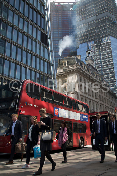 Pollution from the chimney of an old building pours out into the atmosphere amongst modern glass buildings in the City of London, London, England, United Kingdom. At street level, busses and traffic passes adding to the emissions, and all adding up to the poor air quality which people are breathing on a daily basis. London is trying to achieve air quality targets. The European Air Quality Index, run by the European Environment Agency EEA and the European Commission, allows users to check the current air quality across Europe's cities and regions. Environmental groups called for the Government to take urgent steps, including creating and funding clean air zones in pollution hotspots.