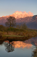 Mount Blanshard (the Golden Ears) is reflected in a pond at the Pitt-Addington Marsh in Pitt Meadows, British Columbia