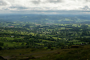 View from Titterstone Clee Hill across agricultural fields on 10th May 2021 in Titterstone Clee Hill, near Ludlow, Shropshire, United Kingdom. Titterstone Clee Hill, sometimes referred to as Titterstone Clee or, incorrectly, Clee Hill, is a prominent hill in the rural English county of Shropshire, rising at the summit to 533 metres above sea level. It is one of the Clee Hills, in the Shropshire Hills Area of Outstanding Natural Beauty.