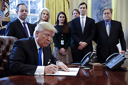 January 24, 2017 - Washington, District of Columbia, United States of America - US President Donald Trump (F), with White House chief of staff Reince Pribus (L), counselor to the President Kellyanne Conway (2L), White House Communications Director Hope Hicks (3L), Senior Advisor Jared Kushner (2R) and Senior Counselor Stephen Bannon (R), signs one of five executive orders  related to the oil pipeline industry in the oval office of the White House in Washington, DC, USA, 24 January 2017. President Trump has a full day of meetings including one with Senate Majority Leader Mitch McConnell and another with the full Senate leadership..Credit: Shawn Thew / Pool via CNP (Credit Image: © Shawn Thew/CNP via ZUMA Wire)