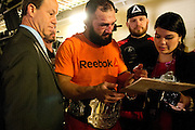 Johny Hendricks signs his paperwork to receive his winnings after earning the UFC Welterweight Championship belt at UFC 171 in Dallas, Texas on March 15, 2014.