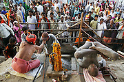 A naga and sadhu at Kumbh Mela in Ujjain, India, doing yoga and giving blessing to people who approach with donations. Kumbh Mela festival, Ujjain, Madhya Pradesh, India. The Kumbh Mela festival is a sacred Hindu pilgrimage held 4 times every 12 years, cycling between the cities of Allahabad, Nasik, Ujjain and Hardiwar. Past Melas have attracted up to 70 million visitors. (Supporting image from the project Hungry Planet: What the World Eats.).