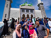 "15 JUNE 2018 - SEOUL, SOUTH KOREA: Muslims from Malaysia pose for ""selfies"" at Seoul Central Mosque on Eid al Fitr, the Muslim Holy Day that marks the end of the Holy Month of Ramadan. There are fewer than 100,000 Korean Muslims, but there is a large community of Muslim immigrants in South Korea, most in Seoul. Thousands of people attend Eid services at Seoul Central Mosque, the largest mosque in South Korea.   PHOTO BY JACK KURTZ"