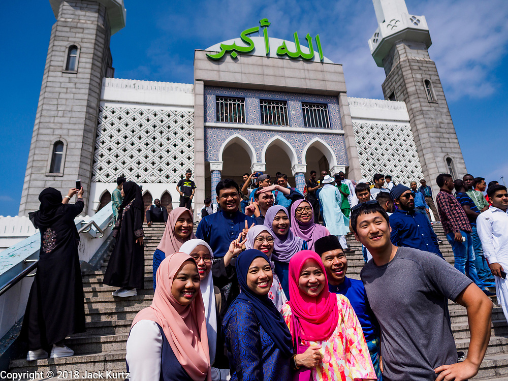 """15 JUNE 2018 - SEOUL, SOUTH KOREA: Muslims from Malaysia pose for """"selfies"""" at Seoul Central Mosque on Eid al Fitr, the Muslim Holy Day that marks the end of the Holy Month of Ramadan. There are fewer than 100,000 Korean Muslims, but there is a large community of Muslim immigrants in South Korea, most in Seoul. Thousands of people attend Eid services at Seoul Central Mosque, the largest mosque in South Korea.   PHOTO BY JACK KURTZ"""