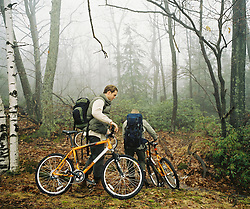 Two friends with backpacks, walking their mountain bikes through a mist covered wooded area