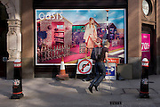 Hopping man on crutches and roadworks signs below an Oasis fashion poster featuring a young woman in a utopian fantasy about to cross a road.