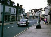 Vintage water pump on High Street, Great Dunmow, Essex 1970 with Ford Consul Classic car