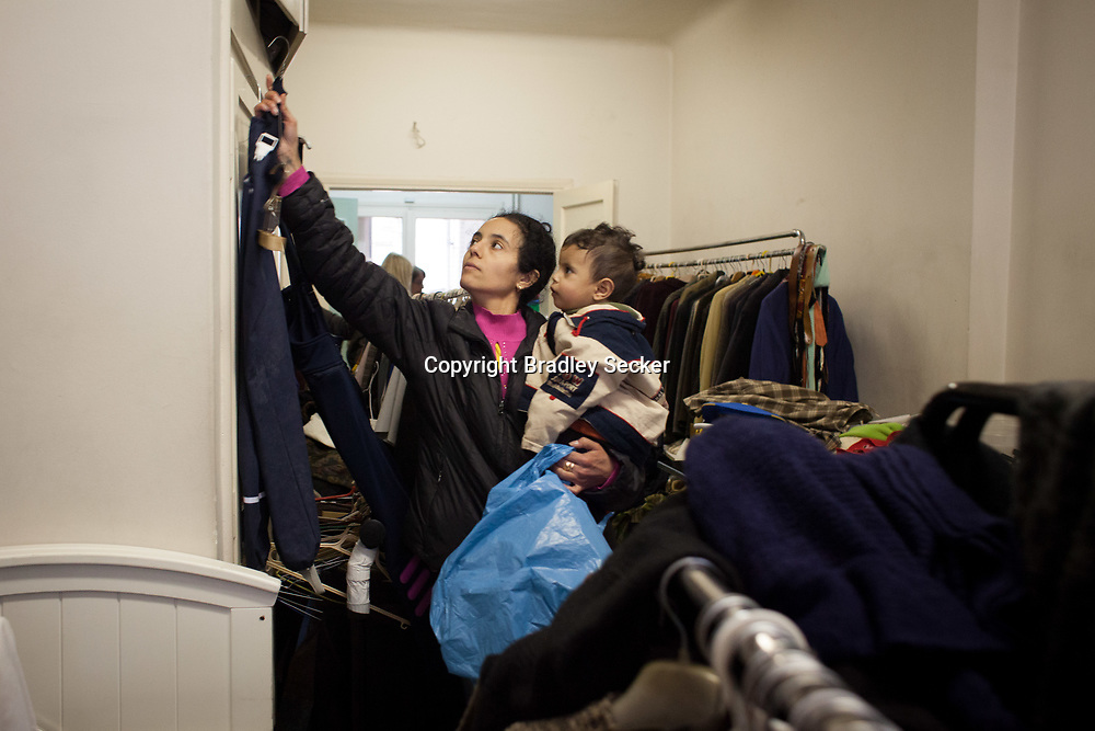 A mother and child choose clothes at the Karitas centre in central Athens. Twice a week, those in need can come and collect clothing donated to the centre. The centre is open to all but predominantly used by migrants and asylum seekers.