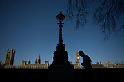 The tower containing Big Ben amid the Gothic architecture of Britain's Houses of Parliament seen from the Embankment. A male jogger passes-by, a silhouette seen aginst the strong power of Parliament on the River Thames. As he runs across the scene, his head appears to be nudging the clock tower of Big Ben, an appearance of false scale. The House of Commons is the lower house of the Parliament of the United Kingdom, which also comprises the Sovereign and the House of Lords (the upper house). Both Commons and Lords meet in the Palace of Westminster.