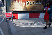 With a sign warning that the footpath (sidewalk) is closed, a pedestrian passes a construction hoarding at a new development called One Crown Place on Sun Street near Liverpool Street Station in the City of London, the capital's financial district - aka the Square Mile, on 8th August, in London, England.