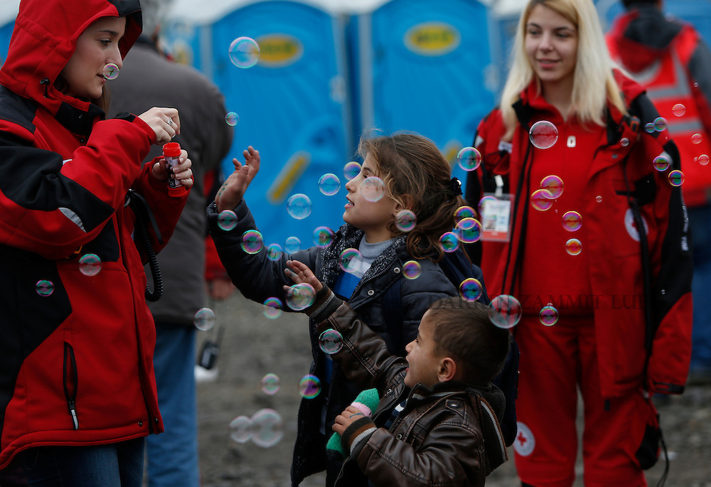 Children play with bubbles blown by volunteers as migrants and refugees are registered by the authorities before continuing their train journey to western Europe at a refugee transit camp in Slavonski Brod, Croatia, February 10, 2016.<br /> Photo: Darrin Zammit Lupi