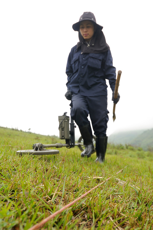 """Mines Advisory Group, Technician, Sia Thorthongyer, age 19, uses a metal detector to uncover live bombs hidden in the soil.  Sia and her partner Vonekham said, """"The first time we found a bomb we were afraid.  But we have good training and team work.  We have found many bombs, now it is just normal.  But, if we see a snake - we drop everything and run!"""" ..Laos was part of a """"Secret War"""", waged within its borders primarily by the USA and North Vietnam.  Many left over weapons supplied by China and Russia continue to kill.  However, between 90 and 270 million fist size cluster bombs were dropped on Laos by the USA, with a failure rate up to 30%.  Millions of live cluster bombs still contaminate large areas of Laos causing death and injury.  The US Military dropped approximately 2 million tons of bombs on Laos making it, per capita, the most heavily bombed country in the world.   ..The women of Mines Advisory Group (MAG) work everyday under dangerous conditions removing unexploded ordinance (UXO) from fields and villages...***All photographs of MAG's work must include (either on the photo or right next to it) the credit as follows:  Mine clearance by MAG (Reg. charity)***."""