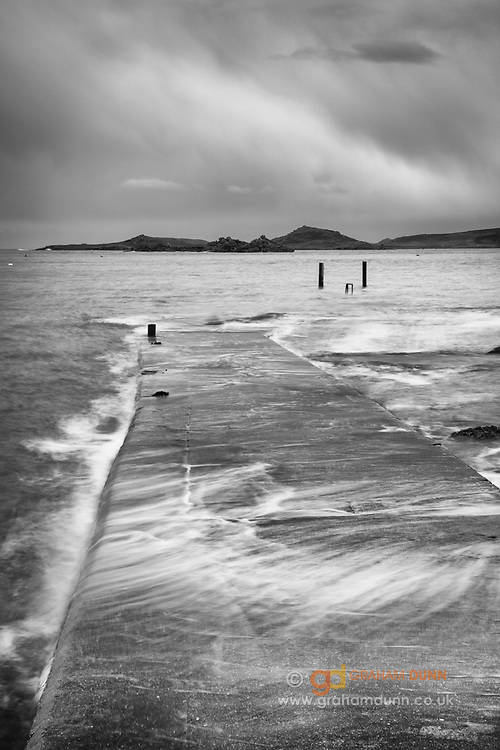 High Spring Tide waters break over Old Grimsby Harbour's wall on Tresco, Isles of Scilly, UK. Dramatic skies hover above Foremans Island in the distance. April, 2016.