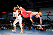 Male wrestler doing flying drop kick move on female opponent in the ring. Lucha Libre wrestling origniated in Mexico, but is popular in other latin Amercian countries, including in La Paz / El Alto, Bolivia. Male and female fighters participate in the theatrical staged fights to an adoring crowd of locals and foreigners alike.