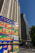 The Woolworth Building and a smoothie fruit drink kiosk on sale at 233 Broadway, New York City. As a cyclist passes-by, we see this mobile business on the pavement (sidewalk) before opening for trade. Colourful images of fruit combinations are be seen wrapped around the sides of the trailer on the street corner in Lower Manhattan. The Woolworth Building, at 233 Broadway, Manhattan, New York City, designed by architect Cass Gilbert and completed in 1913, is an early US skyscraper, designed in the neo-Gothic style by the architect Cass Gilbert for the company's new corporate headquarters on Broadway,  opposite City Hall. Originally designed to be 420 feet (130 m) high, the building was eventually elevated to 792 feet (241 m). At its opening, the Woolworth Building was 60 stories tall and had over 5,000 windows.