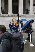 Pedestrians and umbrellas during a sudden downpour in Trafalgar Square, on 13th August 2018, in London, England.