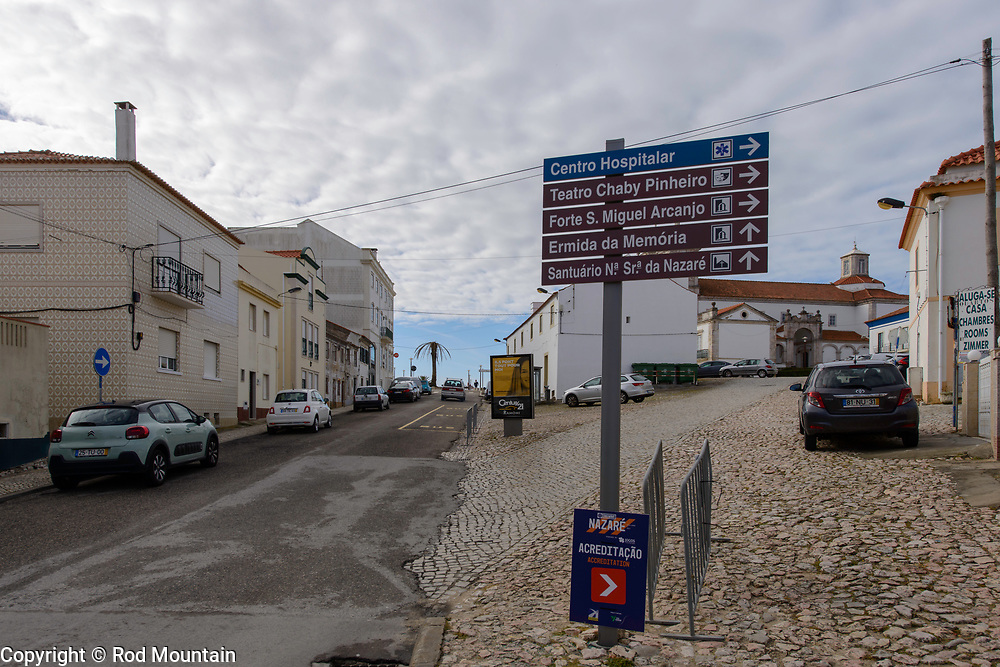Big Wave Accreditation<br /> <br /> Nazaré, Portugal - February 12, 2018 - A Big Wave Accreditation sign is temporarily posted to bottom of a directional sign post. Safety is paramount as  many surfers from around the world are drawn to  the local surf, due to very high breaking waves caused by the underwater Nazaré Canyon. Nazaré is one of the most popular seaside resorts in the Silver Coast, Portugal. <br /> <br /> Image: © Rod Mountain<br /> <br /> http://www.rodmountain.com<br /> [l] <br /> <br /> Nikon D800 / Nikkor Lens<br /> @nikoncanada #NikonCA<br /> @NikonUSA #NikonNoFilter<br /> @nikoneurope #NikonEurope<br /> <br /> https://www.visitportugal.com/en<br /> @visitportugal <br /> <br /> https://en.wikipedia.org/wiki/Nazaré,_Portugal<br /> http://www.cm-nazare.pt/en<br /> @municipiodanazare @cmnazare @CMNazareMata <br /> <br /> @b.w.r.a.g @BWRAG<br /> #portugal #culturaportugesa #turismoemportugal #turismo #rotaportugal #Nazare<br /> <br /> #everydayportugal #visitportugal #tourismportugal #blacknwhitepic #ic_bw_bw #byn #monochrome #bnwphotography #bnw_planet #bwstyles_gf #streets_storytelling #zonestreet <br /> <br /> #trip #getaway #sharetravelpics#worldtravelpics #stayandwander #ourplanetdaily #LetsGoEverywhere #travelandlife