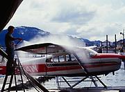 Alaska Island Air pilot Doug Riemer washing Cessna 180, Petersburg, Alaska.